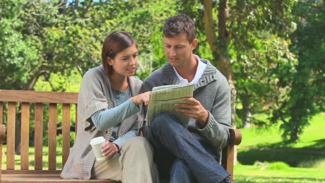 vídeos y material grabado en eventos de stock de young couple doing a crossword / cape town, western cape, south africa - crucigrama