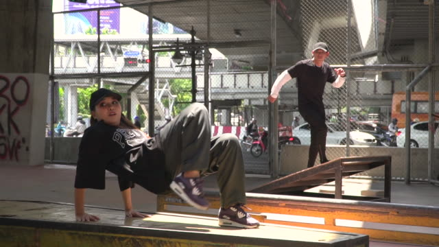 young couple doing break dance under the bridge - fashionable stock videos & royalty-free footage