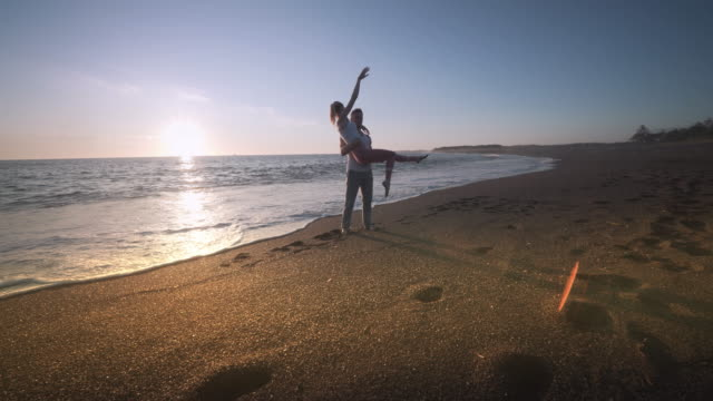 young couple doing power moves gymnastics at sunset, bandon, oregon - power in nature点の映像素材/bロール