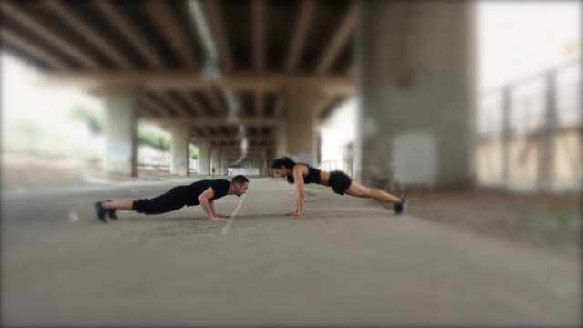 young couple doing push-ups together in the city - high street stock videos & royalty-free footage