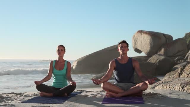 young couple doing yoga on beach - 2人点の映像素材/bロール