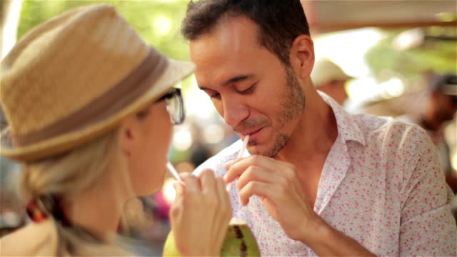 young couple drink from coconut and kiss sweetly at sunny rio outdoor market - coconut stock videos & royalty-free footage