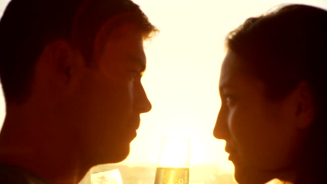 CU Young couple drinking champagne and kissing standing by window at sunset, Brooklyn, New York City, New York State, USA