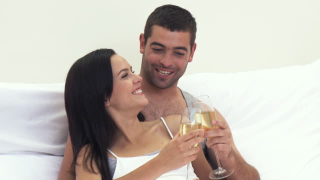 stockvideo's en b-roll-footage met ms young couple drinking champagne in bed / cape town, south africa - achterover leunen