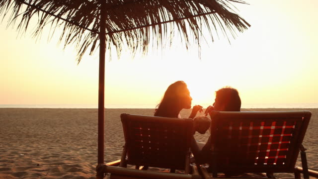 vídeos de stock, filmes e b-roll de young couple drinking coconut water on the beach - parélio