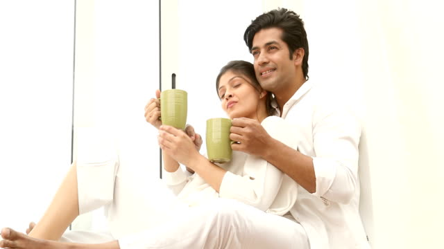 stockvideo's en b-roll-footage met ms young couple drinking coffee and talking while sitting on window sill at home / delhi, india - vensterbank