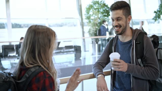 young couple drinking coffee at the airport and talking while waiting for the flight - slovenia stock videos & royalty-free footage