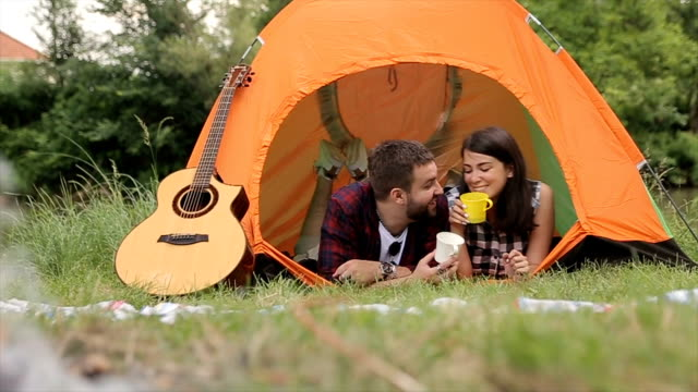 Young couple drinking coffee in the tent,dolly shoot