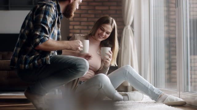 young couple drinking coffee together at home - living room stock videos & royalty-free footage