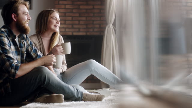 Young couple drinking coffee together at home