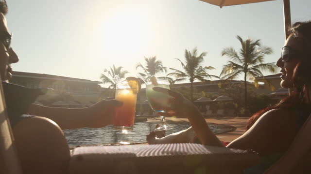 vídeos de stock e filmes b-roll de young couple drinking juice in a resort - ao lado da piscina