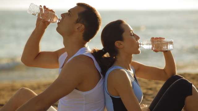 young couple drinking water on beach