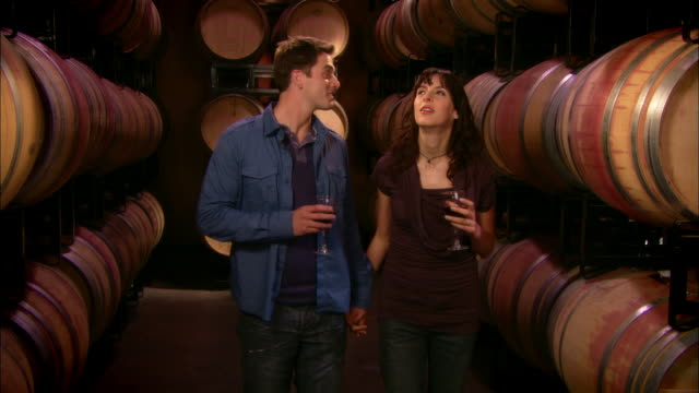 MS Young couple drinking wine near casks in wine cellar / Paso Robles, California, USA