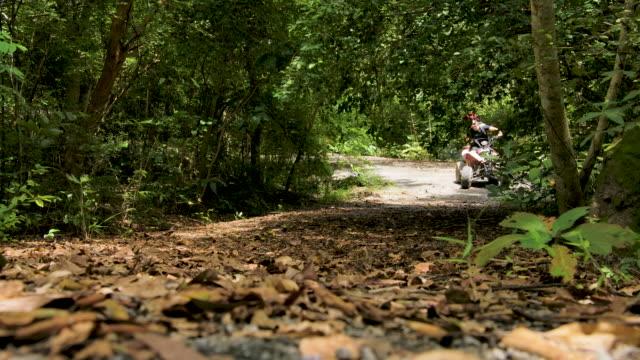 ungt par kör atv i skogen. - partire bildbanksvideor och videomaterial från bakom kulisserna