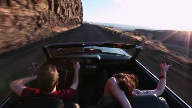 vídeos de stock e filmes b-roll de ws young couple driving convertible at sunset on desert road/washington, usa  - convertible