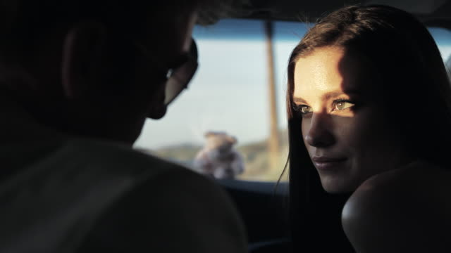 ms young couple driving in car, woman looking into eyes of young man and man touching face and hair / palmdale, ca, united states - liebe stock-videos und b-roll-filmmaterial