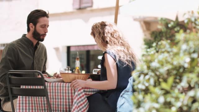 young couple eating alfresco - 対面点の映像素材/bロール