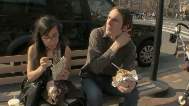 ms young couple eating falafels on bench on new york street downtown /  jersey city, new jersey, usa - ジャージーシティ点の映像素材/bロール