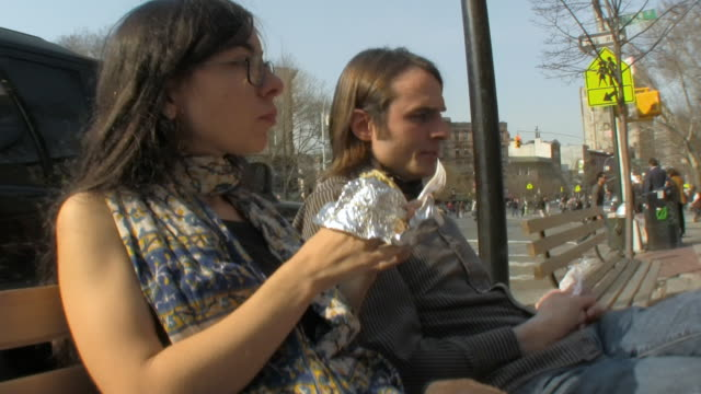 MS Young couple eating falafels on bench on New York street downtown /  Jersey City, New Jersey, USA