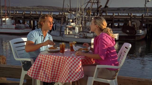 ms, young couple eating fish and chips in harbor, morro bay, california, usa, - アイスティー点の映像素材/bロール