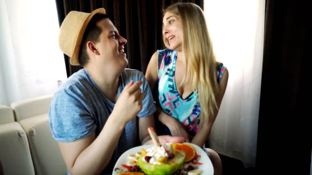 Young couple eating fruit salad