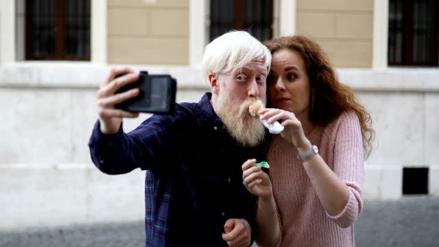 vídeos de stock, filmes e b-roll de pares novos que comem o gelato na cidade e que tomam o selfie - fofo descrição geral
