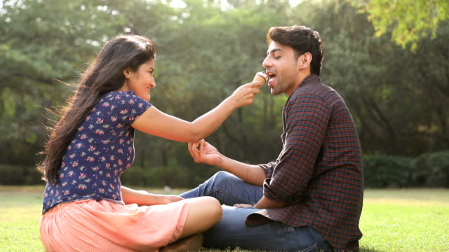 young couple eating ice cream in the park, delhi, india - ice cream stock videos & royalty-free footage