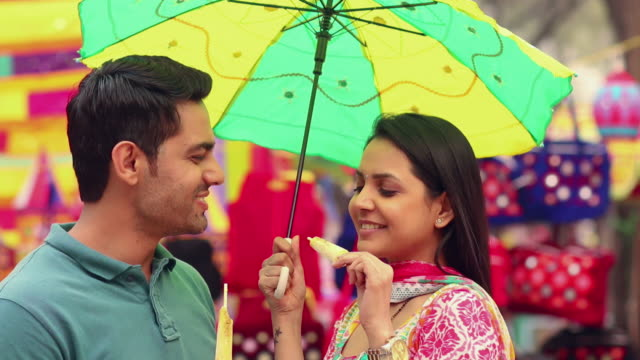 young couple eating kulfi ice cream, suraj kund fair, faridabad, haryana, india - moving activity stock videos & royalty-free footage