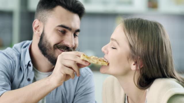 vídeos de stock, filmes e b-roll de jovem casal comendo pizza - barba