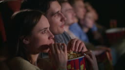 Young couple eating popcorn from one box. Fiends couple watching movie