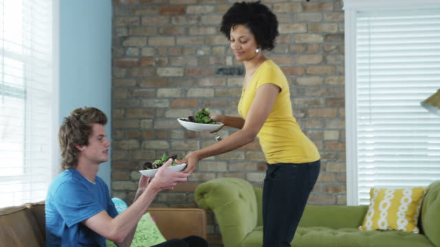 young couple eating salad while watching television