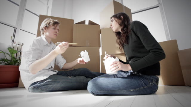 ms la young couple eating take out food, sitting on floor in empty apartment - take away food stock videos and b-roll footage