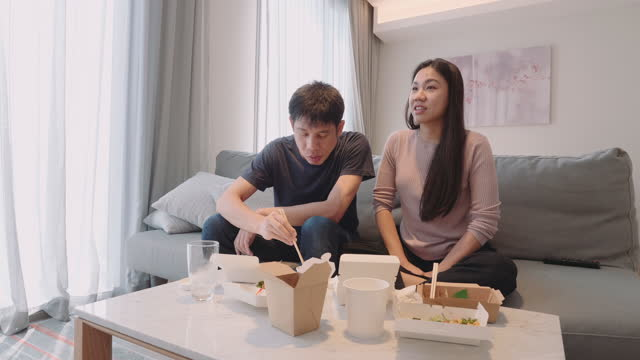 young couple eating take-away food at their home - box container stock videos & royalty-free footage