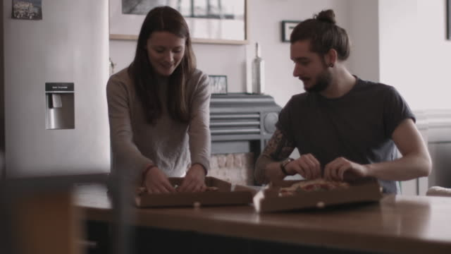 vídeos de stock e filmes b-roll de young couple eating takeout pizza at home - comida de viagem