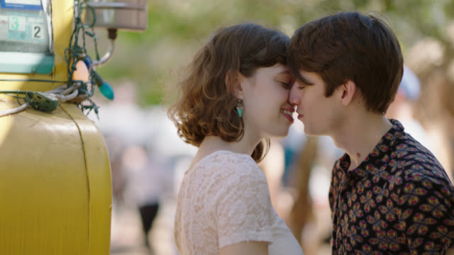 young couple embrace and kiss at an outdoor festival. - coppia di giovani video stock e b–roll