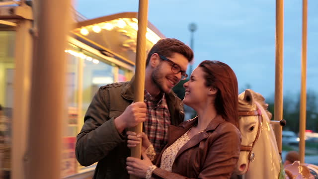 young couple embrace and nuzzle on romantic carousel ride by the eiffel tower. - eiffel tower paris stock videos & royalty-free footage