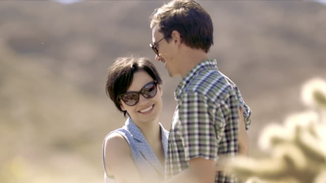 young couple embrace in desert cactus grove - cute cactus stock videos & royalty-free footage