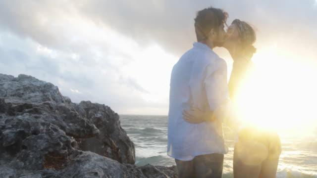 Young couple embrace standing on rocks looking out to sea.