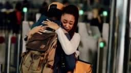 Young couple embracing and crying during emotional farewell at airport