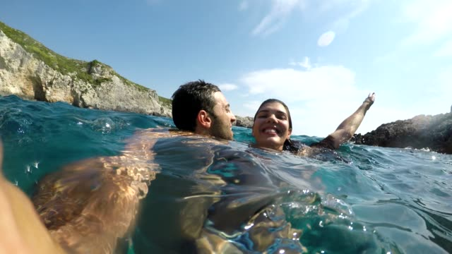 vídeos de stock e filmes b-roll de young couple embracing and taking a selfie at beach in zakynthos - lua de mel