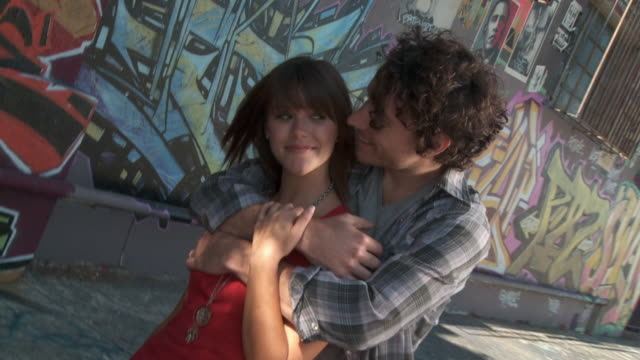 cs, zi, cu, young couple embracing in front of graffiti wall, los angeles, california, usa - 横目点の映像素材/bロール