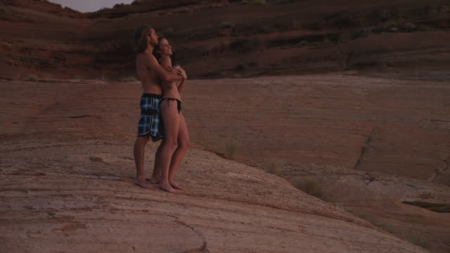 wstu young couple embracing on rock near lake powell, sunset / utah, usa - lake powell stock videos and b-roll footage
