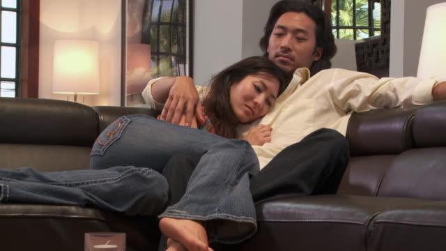 zi, cu, young couple embracing on sofa, los angeles, california, usa - 恋に落ちる点の映像素材/bロール