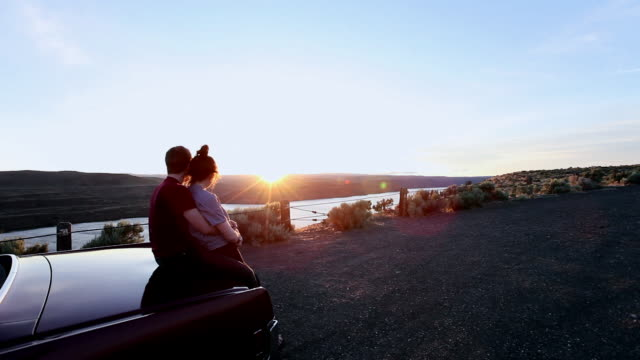 vidéos et rushes de ms young couple embracing on trunk of convertible watching sunset from overlook/washington, usa  - romantisme
