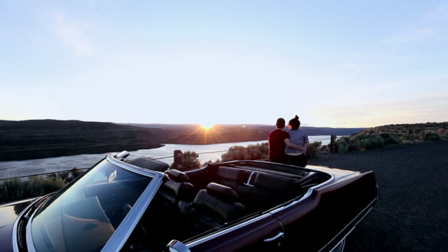 MS Young couple embracing on trunk of convertible watching sunset from overlook rear view/Washington, USA