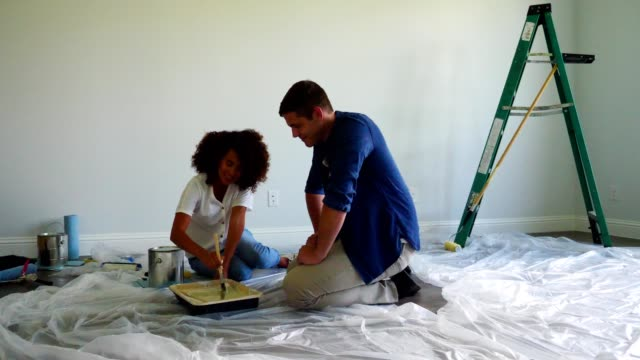 young couple enjoy a diy project in their new home - ethnicity stock videos & royalty-free footage