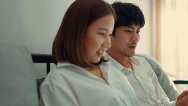 vídeos de stock e filmes b-roll de young couple enjoy home shopping together on laptop while resting on sofa. - viciado em compras