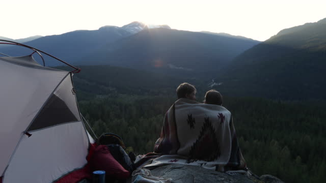 young couple enjoy sunset from tent camping site, on rock ledge - two people stock videos & royalty-free footage