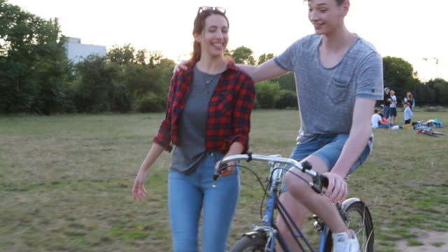 Young couple enjoying a bike ride in the park