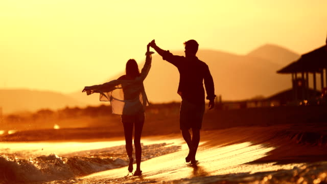 young couple enjoying a romantic sunset on the beach. - leaving stock videos & royalty-free footage